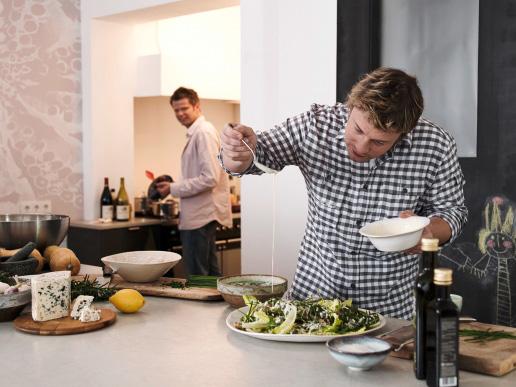Jamie gibt die Salatsoße über den Salat Jörg im Hintergurnd